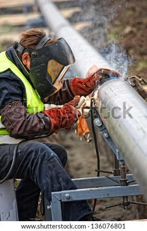 Welder wearing protective clothing for welding industrial construction oil and gas or water and sewerage plumbing pipeline outside on site - stock photo