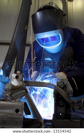Welder welding a car part in an automobile factory - stock photo