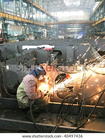 Welder welding a metal part in a dark industrial environment.