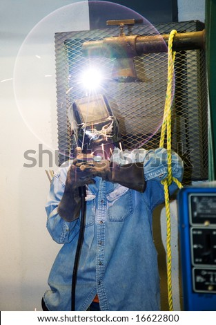 Welder welding a piece of metal overhead.  The circular glow of the lens flare is an intentional part of the composition.  (design on the welders helmet was painted by him, not trademark or logo) - stock photo