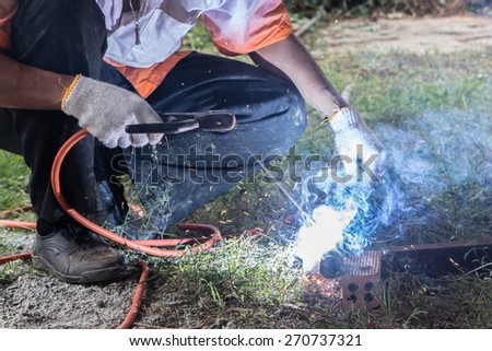 Welder welding steel outdoor site