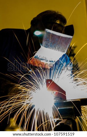 Welder welding steel with sparks - stock photo