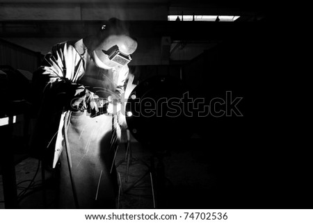 Welder with protective equipment weld metal pipes in factory - stock photo