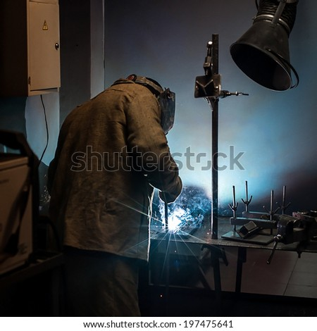 Welder with protective mask working in a steel factory - stock photo