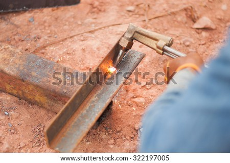 Welder worker in fireproof  cutting metal sheet with propane oxygen gas blow torch burner outdoor.Selective focus. Very shallow Depth of Field, for soft background. - stock photo