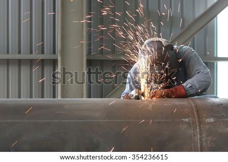 Welder worker is welding a big valve body - stock photo