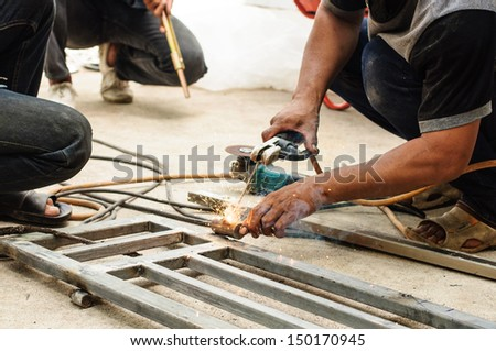 welder worker welding metal by electrode with bright electric - stock photo