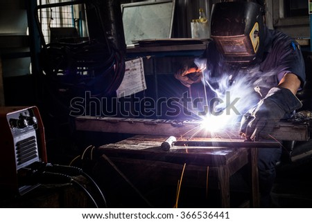 Welder working a welding metal with protective mask and sparks