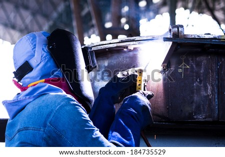 Welder working a welding metal work with protective mask and sparks for construction - stock photo