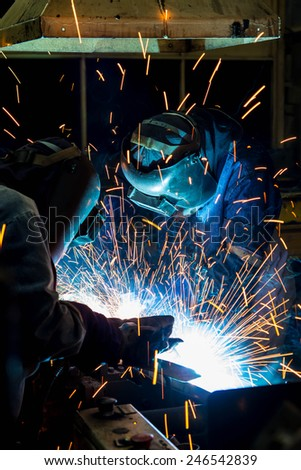 Welder working in a steel factory with sparks flying - stock photo