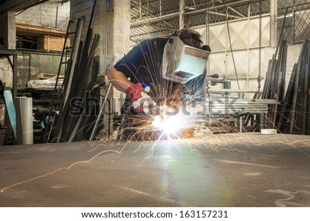 Welder working in a steel factory with sparks flying on working table - stock photo