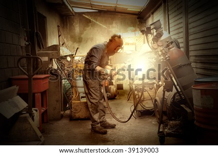welder working in his workshop - stock photo