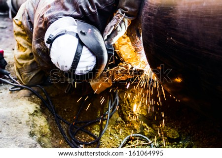 Welder working on a pipeline in construction site wearing overall and safety equipment - stock photo
