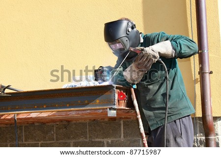 welder working outside in the metal construction, site - stock photo