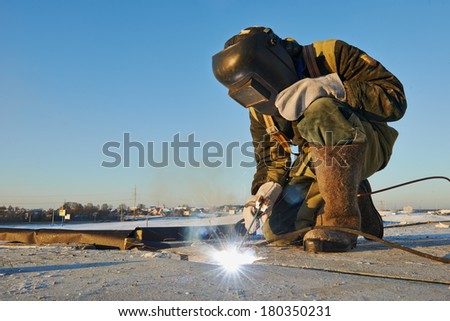 welder working with electrode at arc werding in construction site winter outdoors - stock photo