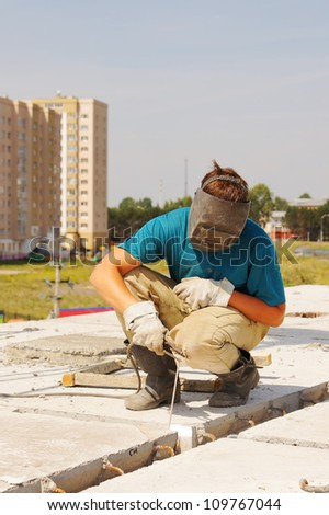 Welder works at the building of a house