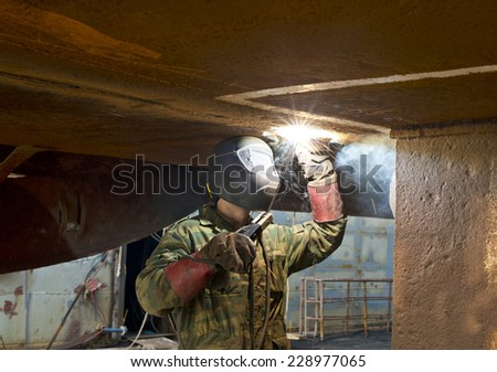 Welders on black metal, repairing a ship in dry dock - stock photo