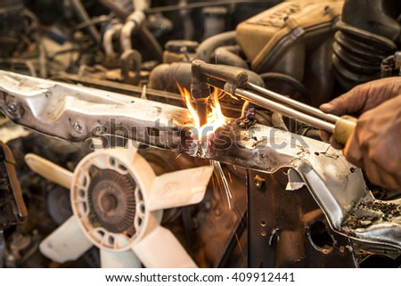 Welders were cutting Automobile chassis of a car in workshop - stock photo