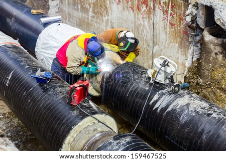 Welders with protective equipment welding outdoors pipeline construction. - stock photo