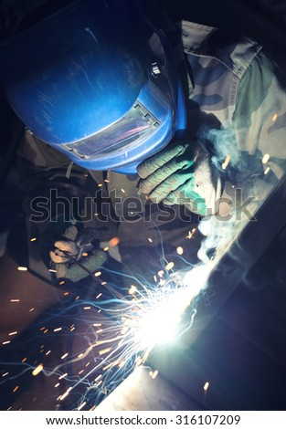 Welding and bright sparks. Concept and idea of hard job - stock photo