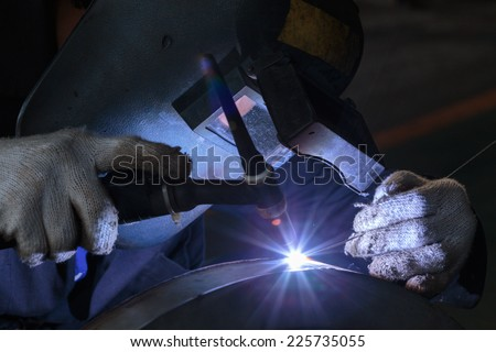 welding metal part in factory. - stock photo
