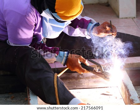 Welding metal structure of building by free hand - stock photo