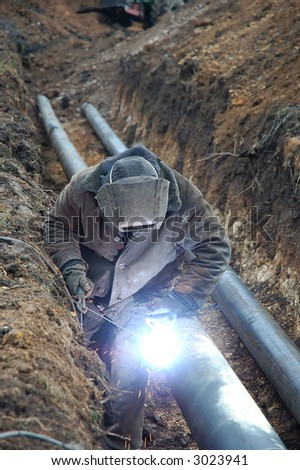 welding operator is working with pipe in earthen hole - stock photo