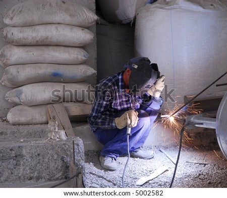 Welding operator on the floor and sparks 2 - stock photo