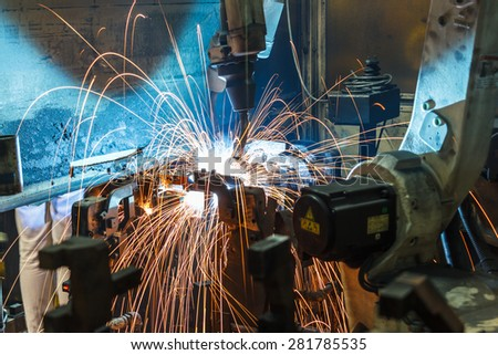 Welding Robot movement in a car factory - stock photo