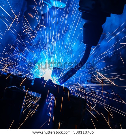 Welding robots movement in a car factory - stock photo