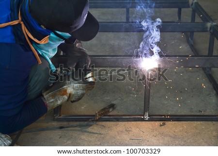 Welding steel with electrode welder - stock photo