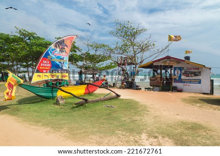 WELIGAMA, SRI LANKA - MARCH 7, 2014: Catamaran, sea food restaurant on the beach. These outlets serve mainly tourists and surfers, working all day and night. - stock photo