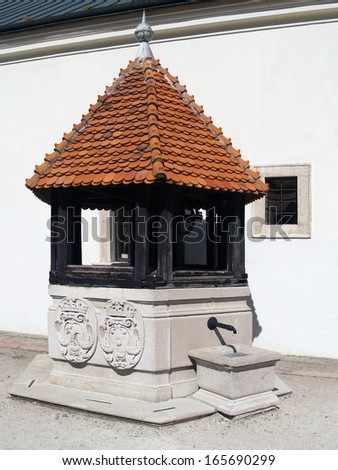 Well at Cerveny Kamen Castle with historical coat of arms of the Palffy family. Cerveny Kamen Castle is 13th century landmark located in southwestern Slovakia.