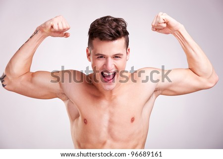 Well-built muscularyoung man with arms raised on studio gray background. model with flexed biceps screaming - stock photo