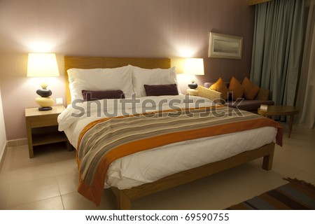 Well decorated hotel bedroom in soft lights - stock photo