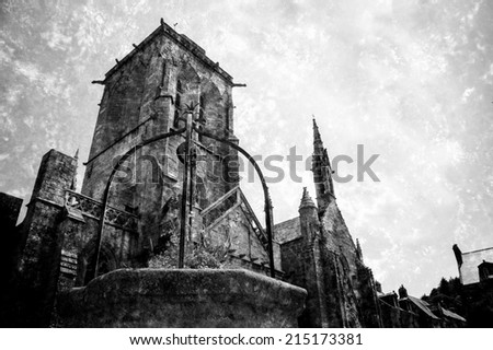 Well decorated with flowers at the square in front of Saint Ronan church in  medieval village Locronan. Brittany, France. Retro aged photo with scratches. Black and white. - stock photo
