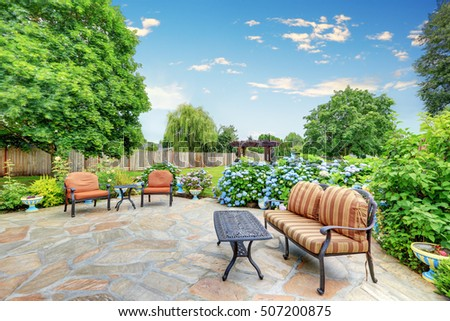 Well Designed Patio Area With Stone Floor In The Backyard Of A Yellow  House. Relaxing