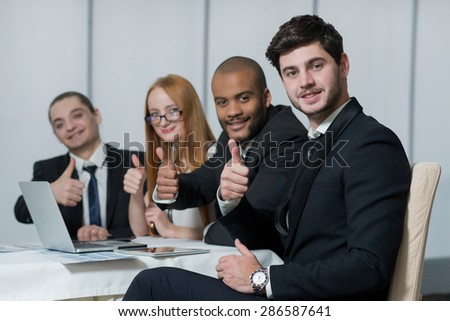 Well done business project. Portrait of confident and motivated businessman working on the project with his team with a smile. All are wearing formal suits. Office business concept - stock photo