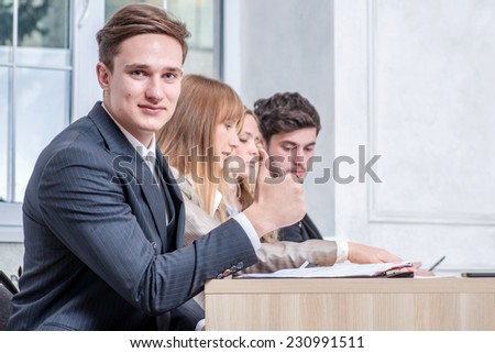 Well done businessman. Smiling businessman sitting at the table and happily shows thumbs up to the camera while his colleague businessmen talking in the background - stock photo