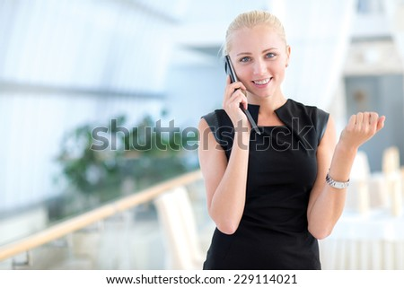 Well done deal on the mobile phone. Young and motivated businesswoman is standing and talking on the mobile phone looking directly into the camera - stock photo