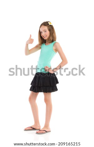 Well done! Young girl in teal shirt and black skirt showing thumb up. Full length studio shot isolated on white. - stock photo