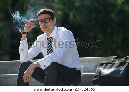 Well dressed business man smoking sitting on a street sidewalk - stock photo