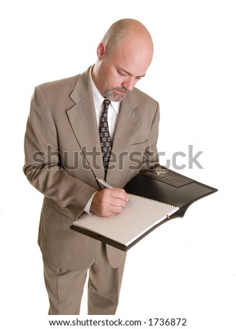well dressed businessman taking notes in a notebook, isolated on a white background.