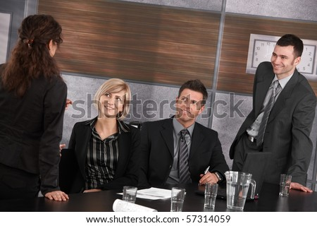 Well dressed businesspeople talking in meeting room, smiling.? - stock photo
