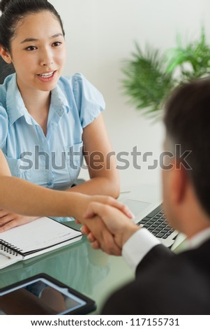 Well-dressed businesswoman shaking man's hand in her office - stock photo