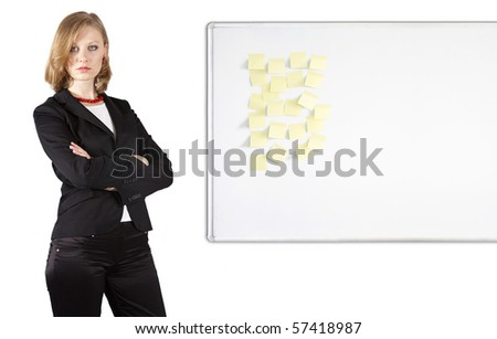 Well-dressed businesswoman with crossed arms is staying near whiteboard with stickers - stock photo