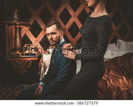 Well-dressed couple in luxury bedroom interior. - stock photo
