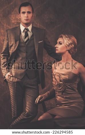 Well-dressed couple in retro interior - stock photo