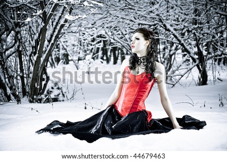 Well-dressed fashion model in red corset sitting alone in winter forest. Professional makeup and hair style. - stock photo