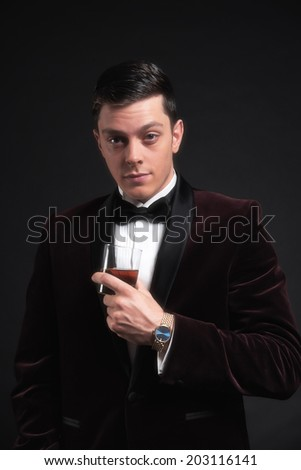 Well dressed good looking business man holding glass of whiskey. Wearing dark red dinner jacket and black bow tie.